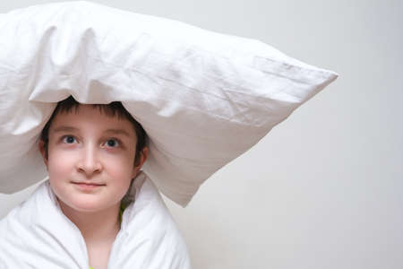 A thoughtful boy in blanket with a pillow on the head Фото со стока
