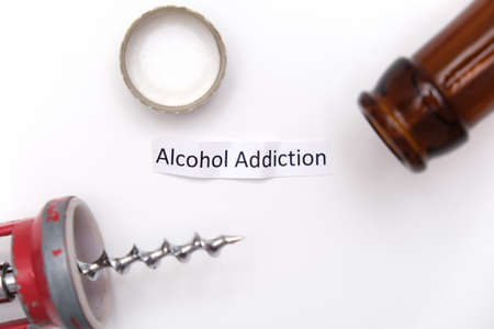 A sign alcohol addiction with a bottle, stopper and corkscrew on white Фото со стока