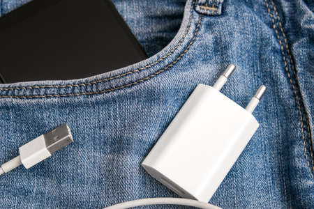Charging smartphone concept, a usb cable for charging devices, gadgets and a phone in a jeans pocket