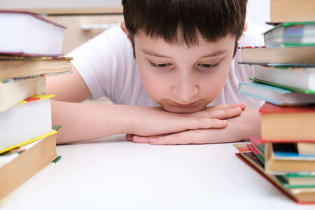 A kid boy sitting at the desk surrounded stacks of books, he is tired of learning and information Фото со стока
