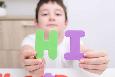 A boy showing a word Hi made of colorful letters, introduction and friendship concept Фото со стока