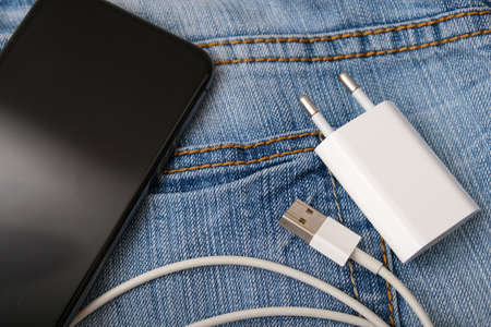 Charging smartphone concept, a usb cable for charging devices, gadgets with adapter plug and a phone on a jeans background Фото со стока