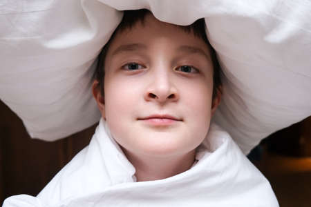 A funny teenage boy in blanket with a pillow on the head, sleeping dreaming concept, close up portrait