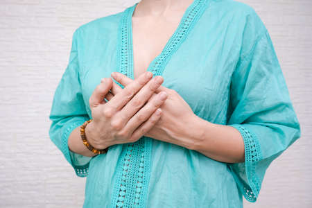 Woman expressing gratitude with hands. Close up image of female hands in prayer position. Saying thank you by hands, grateful woman in ethnic clothes