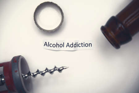 A sign alcohol addiction with a bottle , stopper and corkscrew on white background, bad habbits overcoming concept Фото со стока