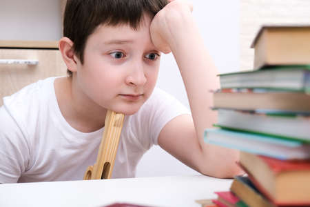 Too much information concept, a boy kid sitting at the desk and holding a toy gun, tired of reading and homework
