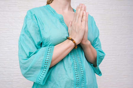 Woman ethnic clothes hold hands together is symbol prayer and gratitude, wai or namaste gesture, sign of thankfulness and and greeting