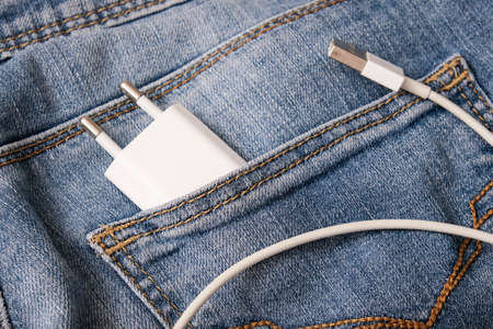 Charging smartphone concept, a usb cable with adapter plug for charging devices, gadgets in a jeans pocket