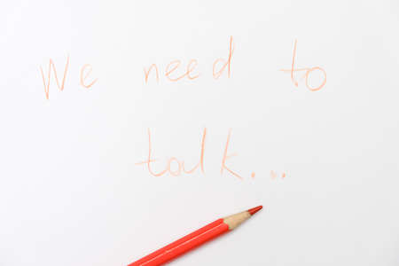 We need to talk message written on white paper, communication problems in family or work office space Фото со стока