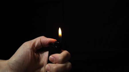 Hand burning flame with a lighter in the dark, black night background, portable device used to create a flame Фото со стока
