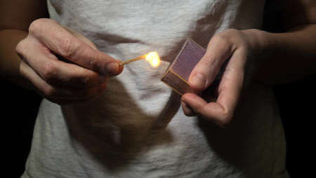 A person, woman lighting match in the dark, hold burning matchstick and a match box in the dark