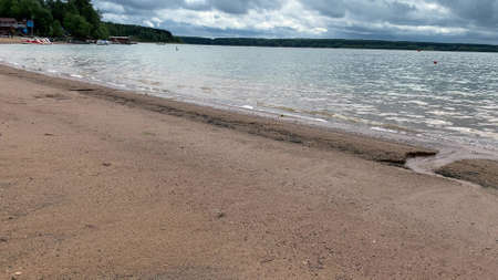 A sandy bank of a lake with clear water and small waves in a cloudy day in summer
