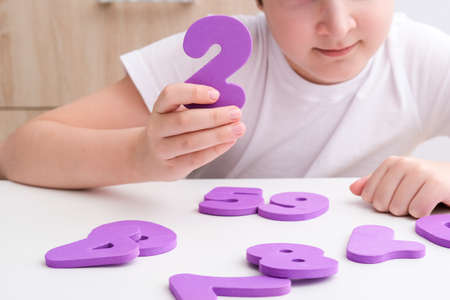 A boy learning math, count exercises at home, holding colorful foam numbers in hand