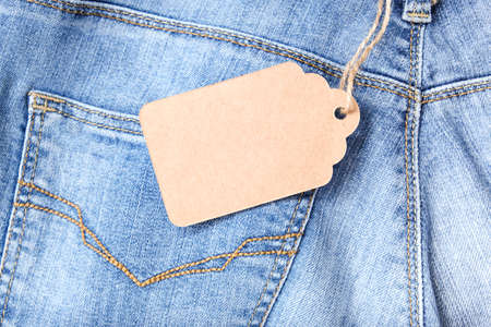 Craft tag, label on blue denim jeans background, copy space