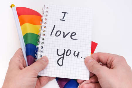 Hands holding a notebook with I Love You inscription and lgbtq rainbow flag on white background Фото со стока
