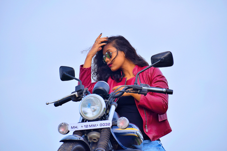 Young Indian girl posing on motorcycle, Pune
