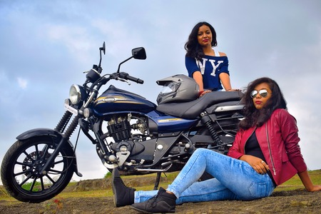 Young Indian girls posing on motorcycle, Pune Stock Photo