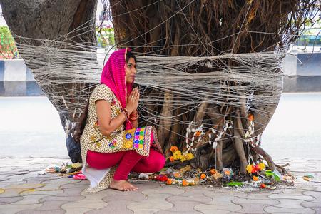Vat Savitri, woman tying thread to Banyan tree and praying. Pune, Maharashtra