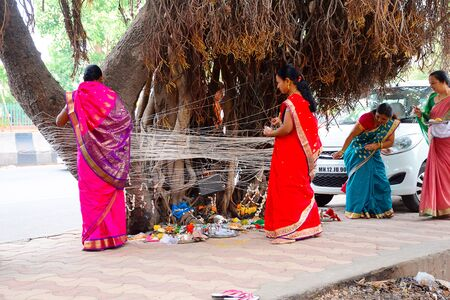 Vat Savitri, women tying thread to Banyan tree. Pune, Maharashtra