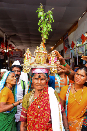 Wari Procession. Woman with tulsi plant on head. Pune