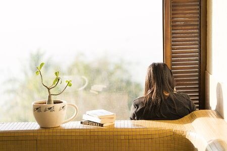 Books with plant and reader