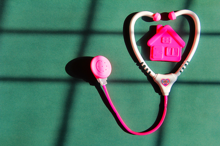 Financial concept with a pink house with pink or toy stethoscope Stock Photo