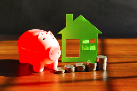 Financial concept with Saving money to buy house or home. Piggy bank with coins