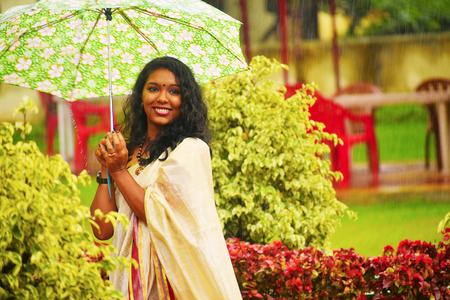 Indian girl In sari walking in the rain with umbrella at Pune, Maharashtra Stock Photo