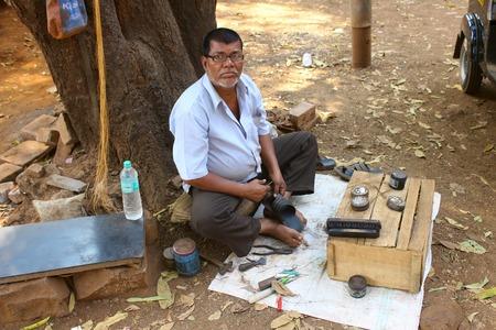 Indian cobbler with his street shop at Khed, Dapoli, Kokan, Maharashtra