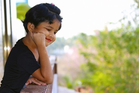 Little girl looking down from balcony with smile on her face at Palande, Kokan Stock Photo