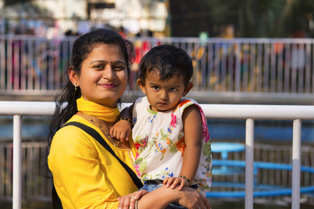Young woman with her daughter smiling at camera, Empress garden at Pune