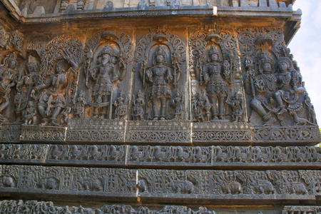 Ornate wall panel reliefs depicting from left a Goddess, Lord Brahma, Mahesh Shiva , lord Vishnu and Shiva-Parvati, Hoysaleshwara temple, Halebidu, Karnataka, India. Stock Photo