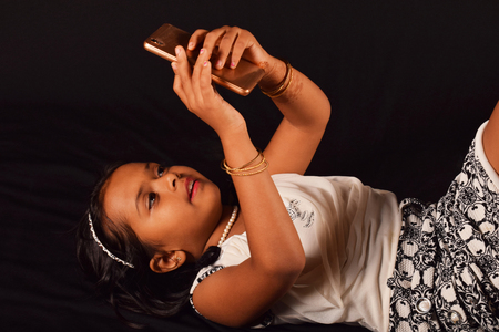 Little girl lying on her back and playing with her mobile phone, Pune, Maharashtra