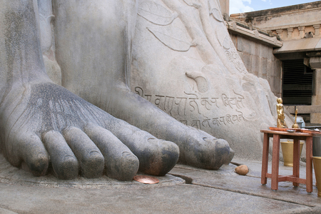 Close up of feet of the statue of Bahubali, also known as Gomateshwara, Vindhyagiri Hill, Shravanbelgola, Karnataka India A golden replica of the monolithic statue is also seen. Stock Photo