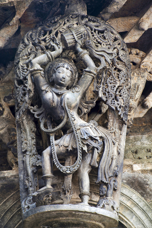 Shilabalika, celestial maiden, as a Dolu Kunita. A lady is palying a drum and dancing . Chennakeshava temple, Belur, Karnataka, India. Notice the hairstyle. Stock Photo