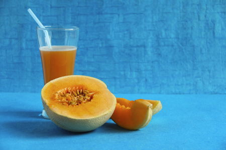 Muskmelon fruit  and juice isolated on light blue background, Pune