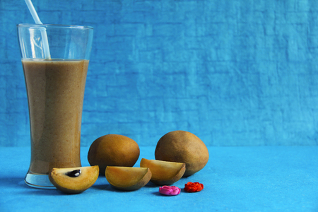Chikoo or sapota with its juice isolated on light blue background, Pune