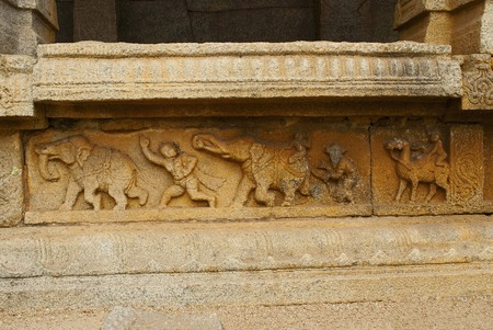Carved figures on the plinth of the inner courtyard, cloisters or pillared verandah. Achyuta Raya temple, Hampi, Karnataka, India. Sacred Center. View from the south.