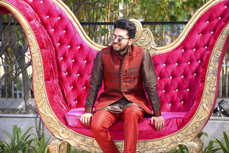 Close up of young man in Indian wedding ceremony attire on sofa, Pune India