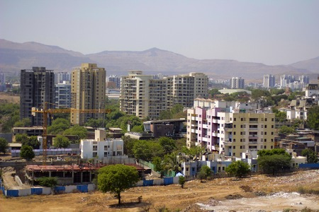 Aerial view of city scape with apartment buildings, under construction buildings and mountains, Pune