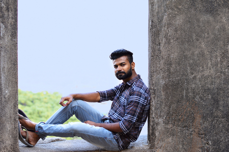 Modelo masculino sentado sobre una repisa de roca mirando a la cámara, el fuerte de Sion, Mumbai, Maharashtra