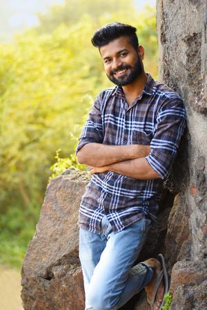 Modelo masculino sonriendo a la cámara descansando sobre una roca. Mumbai, Maharashtra
