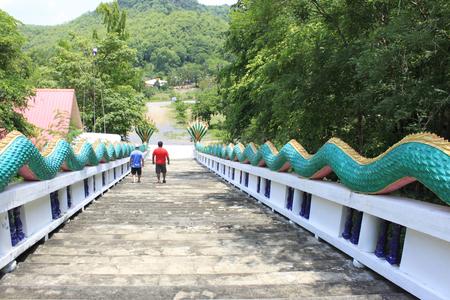 Two tourists climbing down the staircase with green dragon railing, at Ban Bung Sam Phan Nok, Phetchabun, Thailand