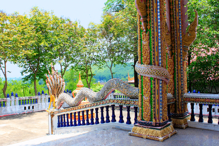 The pillars and dragon railings are colorful and made of mosaic tiles and tiny mirrors. The colors used are red, blue, green and gold at Ban Bung Sam Phan Nok, Phetchabun, Thailand Фото со стока