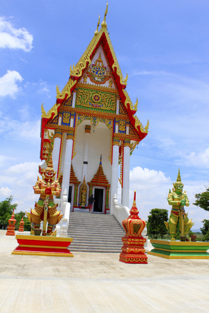Front view of the red and white temple with the guards and steps leading to the main idol inside at Buang Sam Phan, Phetchabun, Thailand