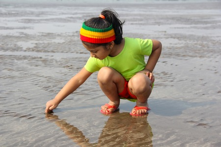 Little girl writing on wet sand at Alibag beach, Konkan, India Stockfoto