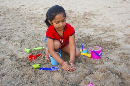 Little girl trying to make a fort with sand on Alibag beach, Konkan, India