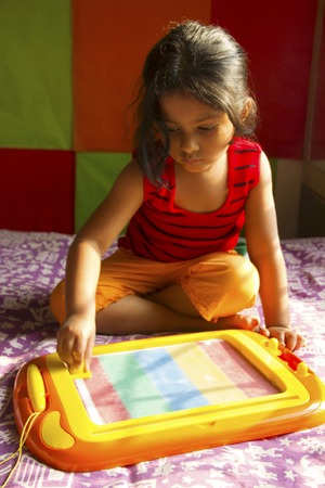 Little girl playing with magnetic drawing board, Pune, Maharashtra, India