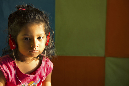 Close-up of little girl listening to music with red colored headphones, Pune, Maharashtra, India 免版税图像