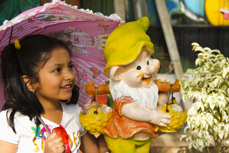 Indian small girl with cartoon statue smiling while holding pink umbrella inside garden, Pune